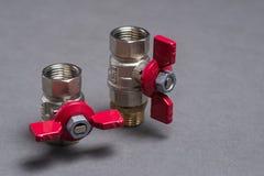 Válvulas del agua con la manija roja en gris Foto de archivo libre de regalías