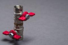 Válvulas del agua con la manija roja en gris Imagenes de archivo
