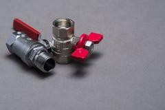 Válvulas del agua con la manija roja en gris Imagen de archivo