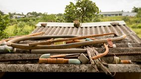 Válvulas e Rusty Metal Junk plásticos abandonados da mangueira das tubulações de água no telhado ondulado sujo - jardim do campo  fotos de stock royalty free