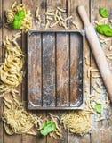 Vária massa italiana cru caseiro e bandeja de madeira no centro Foto de Stock Royalty Free