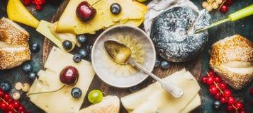 Vária placa de queijo com mergulho do mel, bagas e bolos, vista superior, Fotos de Stock Royalty Free