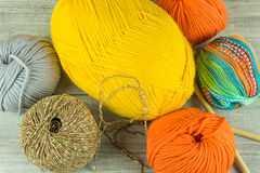 Várias bolas de lãs das cores em uma caixa de madeira com agulhas de confecção de malhas Imagens de Stock Royalty Free
