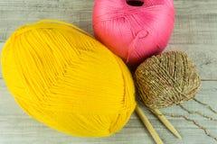 Várias bolas de lãs das cores em uma caixa de madeira com agulhas de confecção de malhas Foto de Stock Royalty Free