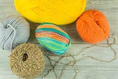 Várias bolas de lãs das cores em uma caixa de madeira com agulhas de confecção de malhas Imagens de Stock