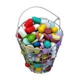 Várias cápsulas dos comprimidos da droga na cesta do ferro Foto de Stock Royalty Free