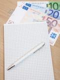 Várias euro- notas ao lado do bloco de notas Fotos de Stock