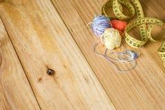 Várias ferramentas da costura, incluindo a fita métrica e as linhas de lãs no fundo de madeira claro foto de stock royalty free