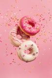 Várias filhóses decoradas no movimento que cai no fundo cor-de-rosa Imagem de Stock