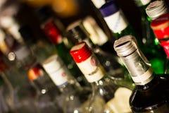 Várias garrafas das bebidas e partes superiores da garrafa Fotos de Stock Royalty Free