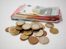 Várias moedas e cédulas do Euro em uma mesa branca Notas e moedas de várias denominações fotos de stock