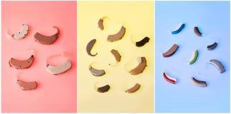 Várias próteses auditivas no fundo amarelo, azul e cor-de-rosa, alternativo à cirurgia Acessório OTORRINOLARINGOLÓGICO imagens de stock