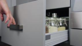 Várias sementes em uns frascos do armazenamento na gaiola, cozinha moderna branca no fundo Organização esperta da cozinha video estoque