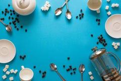 Vário café que faz acessórios: Imprensa do café, copos, pires, feijões de café, colheres e açúcar franceses no fundo do papel azu imagens de stock royalty free