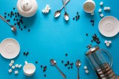 Vário café que faz acessórios: Imprensa do café, copos, pires, feijões de café, colheres e açúcar franceses no fundo do papel azu fotografia de stock royalty free