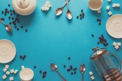 Vário café que faz acessórios: Imprensa do café, copos, pires, feijões de café, colheres e açúcar franceses no fundo do papel azu fotos de stock