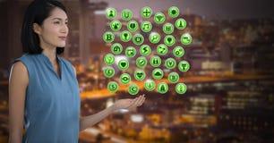 Vários ícones e homem de negócios do app com a palma da mão aberta na cidade na noite Fotos de Stock Royalty Free