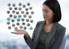 Vários ícones e mulher de negócios do app com a palma da mão aberta no escritório de cidade Foto de Stock Royalty Free