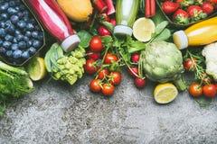 Vários batido e sucos coloridos em umas garrafas com os vegetais e frutos orgânicos frescos no fundo concreto cinzento, vista sup Fotos de Stock