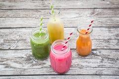 Vários batidos de fruta coloridos nas garrafas de vidro Fotografia de Stock Royalty Free