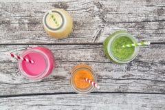 Vários batidos de fruta coloridos nas garrafas de vidro Fotos de Stock Royalty Free