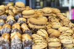 Vários biscoitos com leite condensado e chocolate derramado na venda em uma loja de doces fotografia de stock royalty free