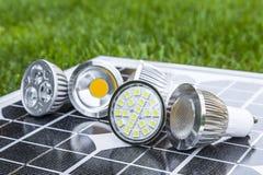 Vários bulbos do diodo emissor de luz GU10 no photovoltaics na grama Foto de Stock Royalty Free