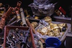 Vários conectores das tubulações de cobre e de aço em uma tabela do encanador dentro fotografia de stock royalty free