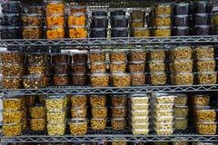 Vários frutos secos e porcas em uns recipientes plásticos que enchem-se acima das prateleiras do metal no suppermarket Imagens de Stock Royalty Free
