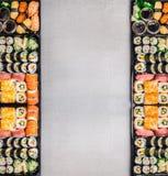 Vários grupos do sushi: rolos, nigiri, maki e uramaki na bandeja de empacotamento preta no fundo de pedra cinzento, vista superio Fotografia de Stock Royalty Free
