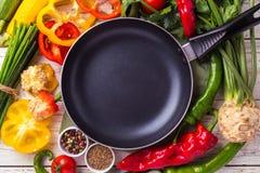 Vários ingredientes dos vegetais na tabela de madeira em torno da frigideira Fotos de Stock