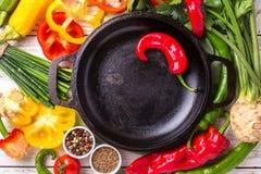 Vários ingredientes dos vegetais na tabela de madeira em torno da frigideira Fotos de Stock Royalty Free