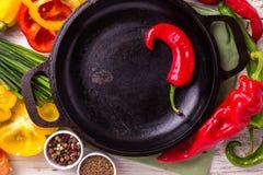 Vários ingredientes dos vegetais na tabela de madeira em torno da frigideira Imagem de Stock