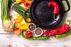 Vários ingredientes dos vegetais na tabela de madeira em torno da frigideira Fotografia de Stock Royalty Free