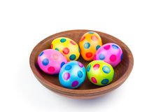 Vários ovos da páscoa pintados da galinha na bacia de madeira no branco imagem de stock