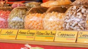 Vários pirulitos redondos no contador do mercado europeu do Natal Nomes alemães dos doces Doces redondos de vitrificação no vidro vídeos de arquivo