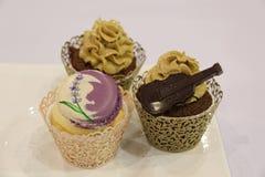 Vários queques: baunilha, chocolate, em uns copos decorativos Fotografia de Stock