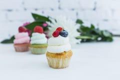 Vários queques com as flores e as folhas frescas das bagas Imagens de Stock Royalty Free