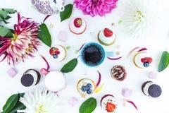 Vários queques com as flores e folhas frescas das bagas, um copo do chá ou café e uma chaleira Vista superior Fotografia de Stock Royalty Free