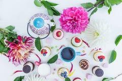 Vários queques com as flores e folhas frescas das bagas, um copo do chá ou café e uma chaleira Vista superior Fotografia de Stock