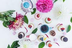 Vários queques com as flores e folhas frescas das bagas, um copo do chá ou café e uma chaleira Vista superior Fotos de Stock Royalty Free