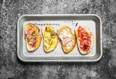 Vários sanduíches com caviar vermelho, bacon, queijo e os legumes frescos em uma bandeja de aço Fotografia de Stock Royalty Free