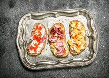 Vários sanduíches com caviar vermelho, bacon, queijo e os legumes frescos em uma bandeja de aço Imagens de Stock Royalty Free