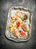 Vários sanduíches com caviar vermelho, bacon, queijo e os legumes frescos em uma bandeja de aço Fotografia de Stock