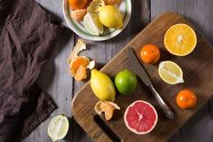 Vários tipos de citrinos em um fundo de madeira escuro Fotos de Stock Royalty Free