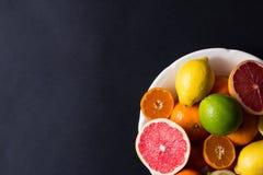 Vários tipos de citrinos em um fundo escuro Fotografia de Stock