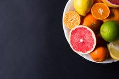Vários tipos de citrinos em um fundo escuro Fotos de Stock