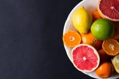 Vários tipos de citrinos em um fundo escuro Foto de Stock