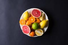 Vários tipos de citrinos em um fundo escuro Foto de Stock Royalty Free