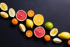 Vários tipos de citrinos em um fundo escuro Imagem de Stock